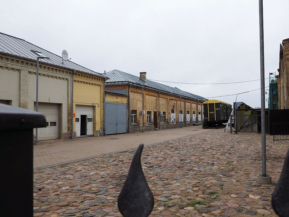 A cobbled courtyard in front with a row of abandoned-looking buildings on the left. Looking down the center a box car is visible in the distance, dark green.
