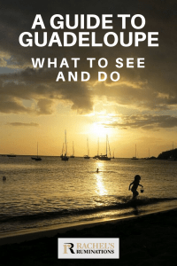 Pinnable image Text: A guide to Guadeloupe: What to see and do Image: Sunset at a beach. Gentle waves in the foreground and the sillhouette of a child running, carrying a pail. On the horizon, silhouettes of moored sailboats. The sun is low in the sky and shines orange through the cloud layer.