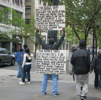 """A man stands in the middle of the sidewalk with his back to the camera. People pass on either side. The man has a sandwich board around his middle with along Bible quote in black paint on white: """"The BIble says Ecclestiates 7.20 For there is not a Just tman upon earth ... etc. Raised above his head with both arms, he holds another sign quoting Ecclesiastes 7.13 and 1.15."""