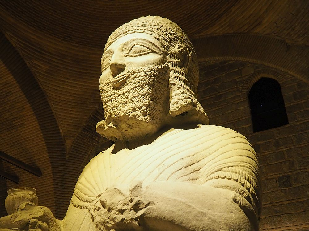 The photo only shows the head and chest of the statue. It has detailed facial hair: the beard is square and carved in neat curls. So is the hair, and a decorative hat is carved with flowers and what looks like decorative lace. The chest is simpler, carved as if he is wearing a cloak that pins in the center of his chest.