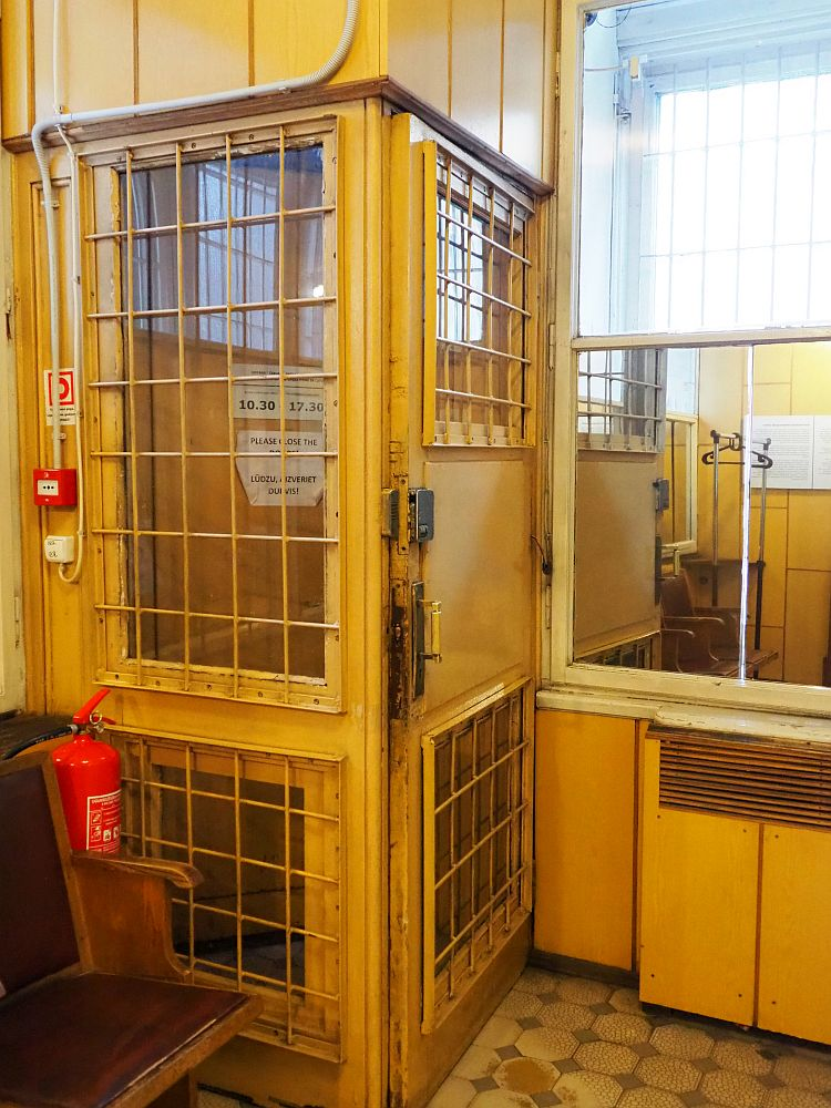 The caged door of the museum. It's about the size and shape of a telephone booth, but barred on the two near sides, with the doors to the street on the other side. It's a sickly yellow color.