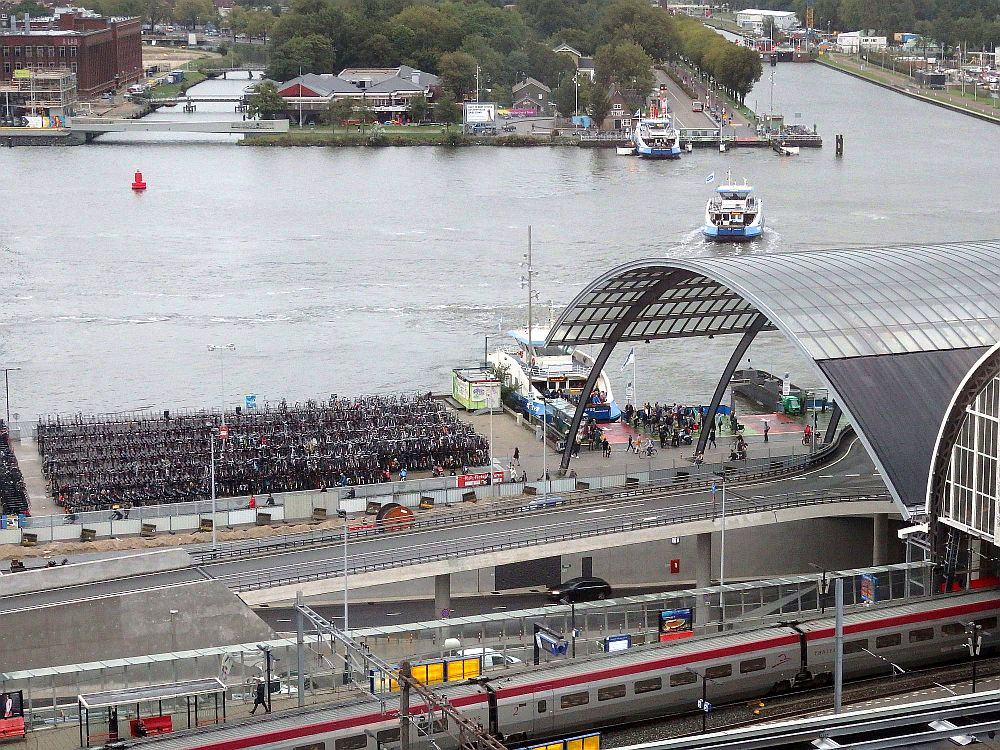Seen from above, in the foreground are a few train tracks crossing the photo horizontally, with one train visible. Beyond that are some road ways, one of which rises on pillars from left to right, going under a curved glass roof on the right side of the photo. Beyond that, back on the ground, a rectangular area next to the river is full of parked bikes and, to the right of that, a small ferry in blue and white is visible. Beyond that, also horizontally, is the river. On the far bank are a few low buildings, and a ferry is halfway across to a small ferry station, where another ferry is moored.