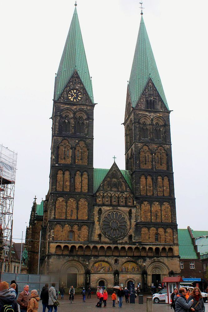 The St. Petri Dom has two very tall spires, both square with green pointed roofs. The building is red brick with archways across the whole ground floor and a rose window centered above the entrance and between the towers.