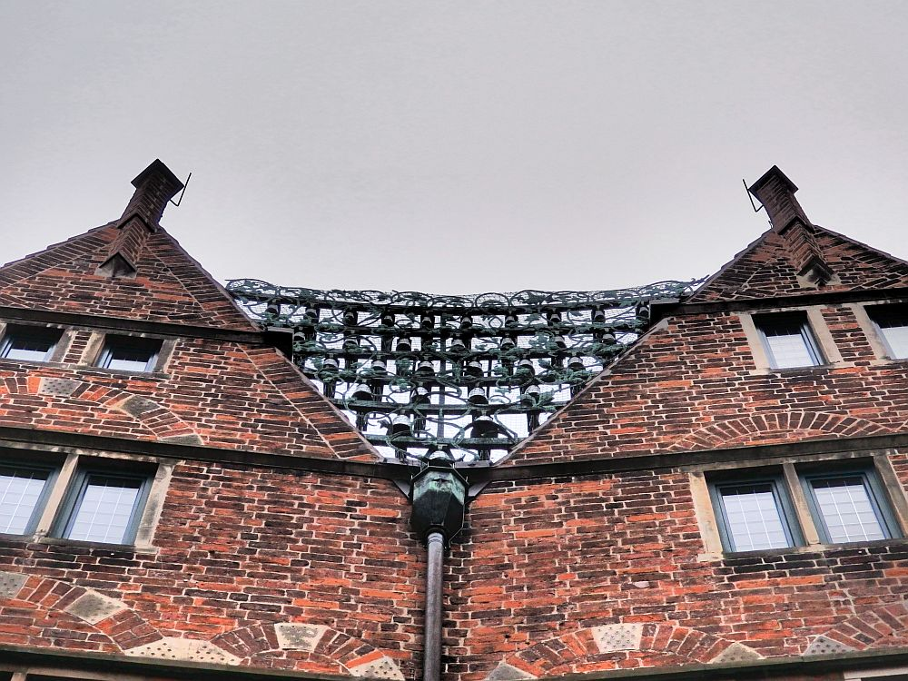 Two pointed top strories of a building. Between them are horizontal bars, from which the small bells hang.