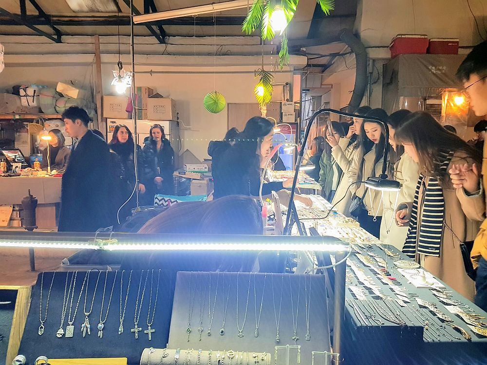In front is a lit case in which necklaces are displayed. Along the right a group of people, mostly young women, are lined up looking at small items (jewelry, I think) on display on tables. On the left part of another stall is visible with a few people walking by.