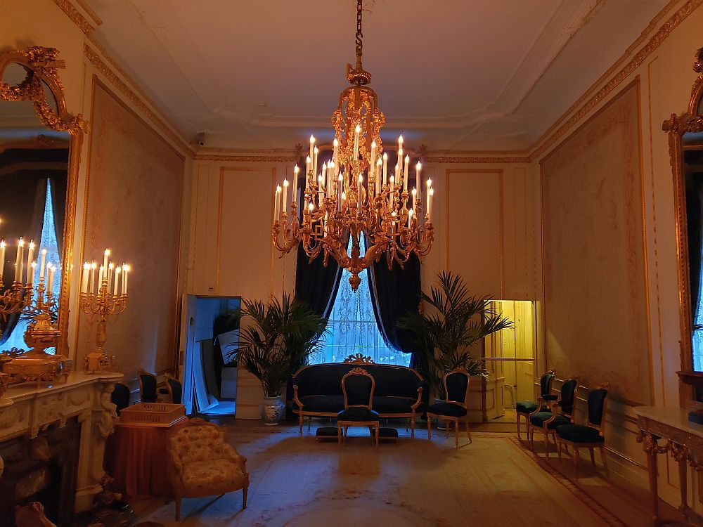 The Willet-Holthuysen Museum's ballroom is a large open room, with the furniture -- mostly just chairs and one sofa, along the walls. A massive chandelier hangs from the center, low enough for a tallish man to bump his head. Behind that is a large window with dark drapes pulled to each side. On the left is a highly-decorated fireplace with a gold-framed mirror above it.