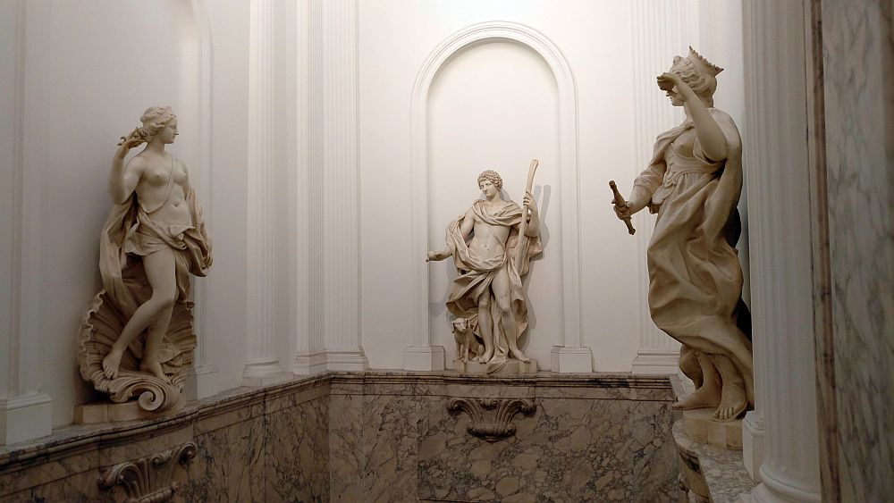 Three classical stone statues perch on a ledge in the Willet-Holthuysen Museum against 3 white-painted walls. On the left, a woman (Venus?) standing on a seashell, her breasts exposed, cloth draped around her waist. Straight ahead, a man, also exposing his middle, with cloth draped around his neck and his waist but, like the Venus, with his legs exposed. A dog peeks from behind his legs. On the right, another similar woman, but wearing a crown and holding what looks to be a flute.