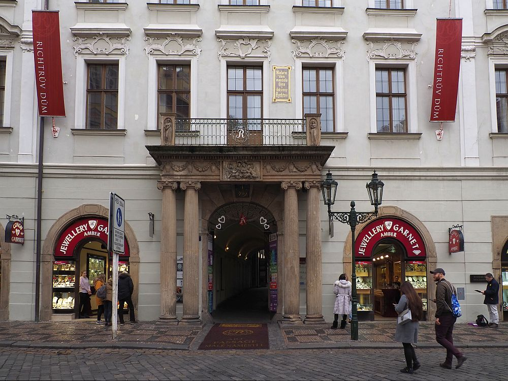 """A typical Prague building with ornate touches above the windows. In the center ground floor is a grand entrance with two pillars on either side supporting a balcony. On either side of the entrance are shops, both with a sign reading """"Jewellery Garnet"""""""