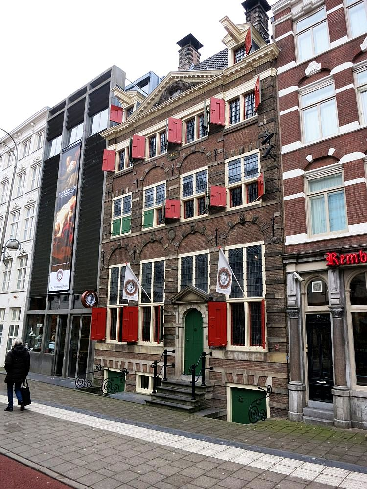 The Rembrandt House Museum is 3 stories high, plus an attic. The windows on the ground floor are tall rectangles while the windows on the upper floors are smaller. the bottom panes of the lower and middle floor windows have open red shutters. The top floor windows and the little attic dormer mindows have shutters that would cover the whole window if closed. The brickwork has an arch over the ground floor windows. the building to the left is, by contrast, dark grey and very minimalistic, with a flat front with a big banner hanging down showing a Rembrandt painting.