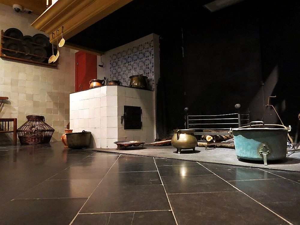 Taken from floor level, the photo shows the bottom of the very large hearth. On the left, a tiled cube that has pots on top of it and a latched door in the side - presumably the oven and stove. Other pots sit on the floor of the hearth.