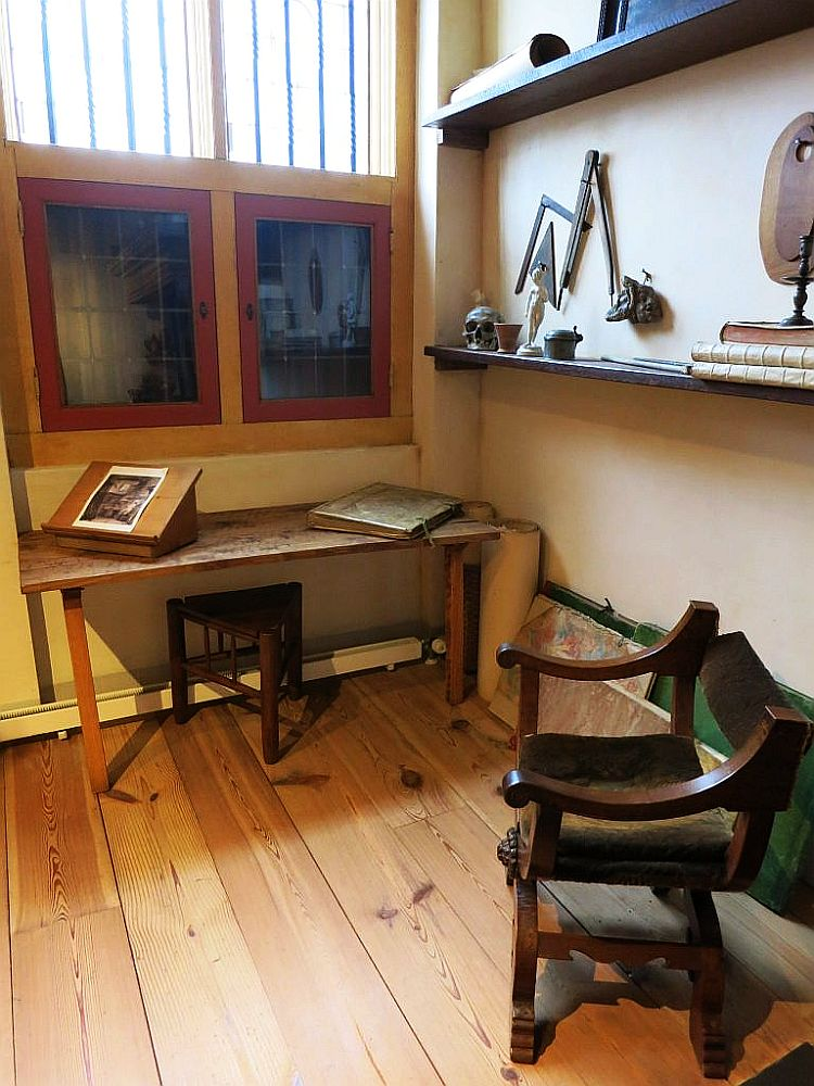 In the foreground, a simple chair with wooden arms and a leather or cloth seat. Behind, against the wall, a simple wooden table with a triangular stool underneath it. It has a lectern with a picture and a large folio bown book sitting on it. Behind that is a window. To the right, above the chair, are some shelves. A few objects on the shelves: a skull, a small figurine, a candlestick, some books, a triangle and a compass. Inside the Rembrandt House Museum.