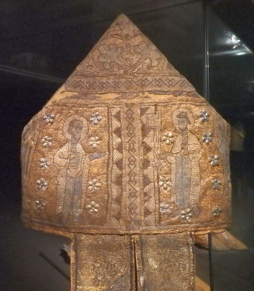 The mitre is square with a triangular point on top and two wide ribbons hanging down. It is entirely covered with embroidery, mostly flowers and abstract shapes except for two men, one on each side, each with a halo.