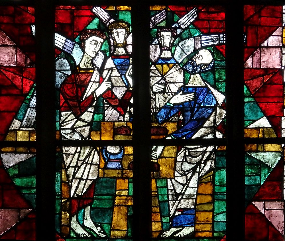 A stained-glass window depicts three angels with wings speaking to a man.