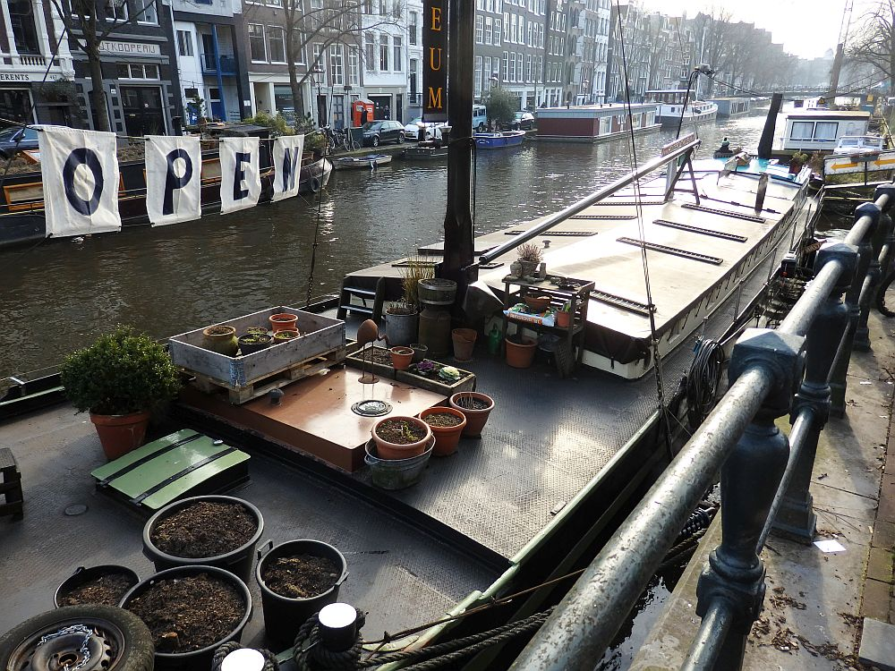 Exterior view of the houseboat. It's low to the water and very long and narrow. On the roof are a bunch of flowerpots; only a few with plants since the photo was taken in the winter. Beyond the boat is a view down the canal, with some other houseboats visible along both banks.