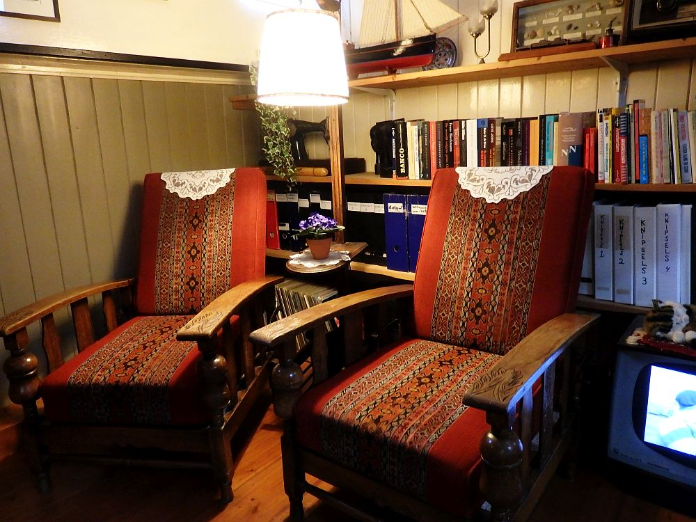 Two wooden chairs with thick red cushions for seat and back, and doilies on the tops. Behind them is a bookshelf lined with books, and, on the top shelf, a model sailboat.