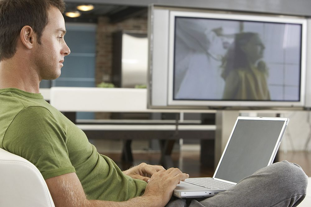 A white man wearing a green t-shirt sits sideways to the camera on an armchair or sofa. He looks at a laptop in his lap. In the background, a large tv is on, showing a vague image of a woman.