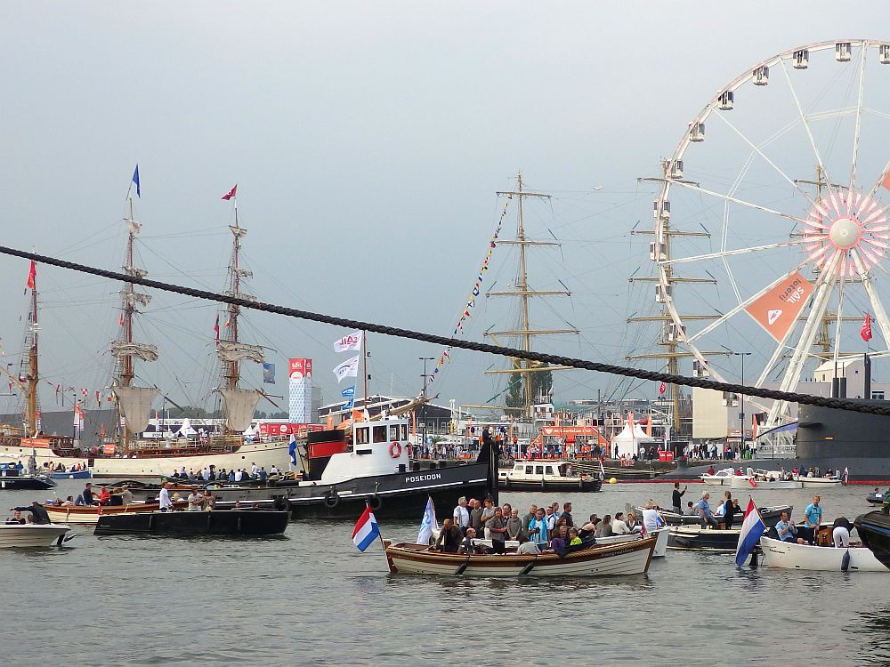 Another general view of the IJ river: Lots of boats passing to the left or the right. In the background a couple of tall ships are visible, moored on the other side. The boats on the river are mostly small, open motorboats. One looks like a tugboat or fishing boat. In the background, part of a ferris wheel is visible.