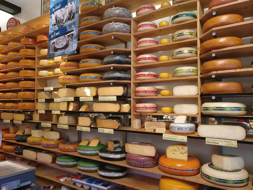 Anothe wall covered with shelves much like bookshelves but closer together. The shelves are filled with wheels of cheese, mostly orange, though some are black, brown or white on the wax outer shell. Most are large wheets, though some are smaller as well. some are cut open, with the exposed cheese covered in plastic wrap.
