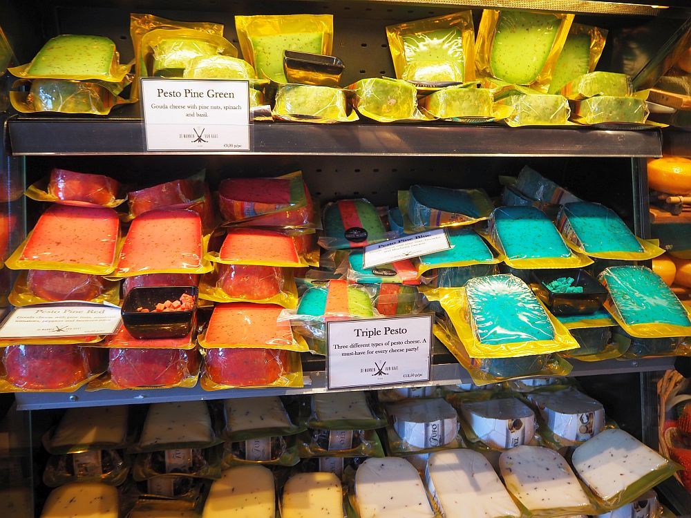 piles of shrink-wrapped cheese wedges: yellow on the tops shelf with a sign reading Pesto Pine Green. Orange and bluish green on the middle shelf, with only one sign visible that says Triple Pesto. The cheeses on the bottom shelf are a more normal color.