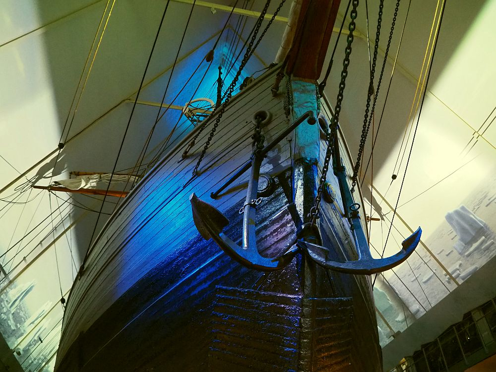 Looking up at a large pointed hull. It looks like it's made of wood planks, though that may not be so. Two large iron anchors hang from chains near the point of the bow. Beyond the boat, images are projected on the two walls of the building: a sea with floating icebergs.