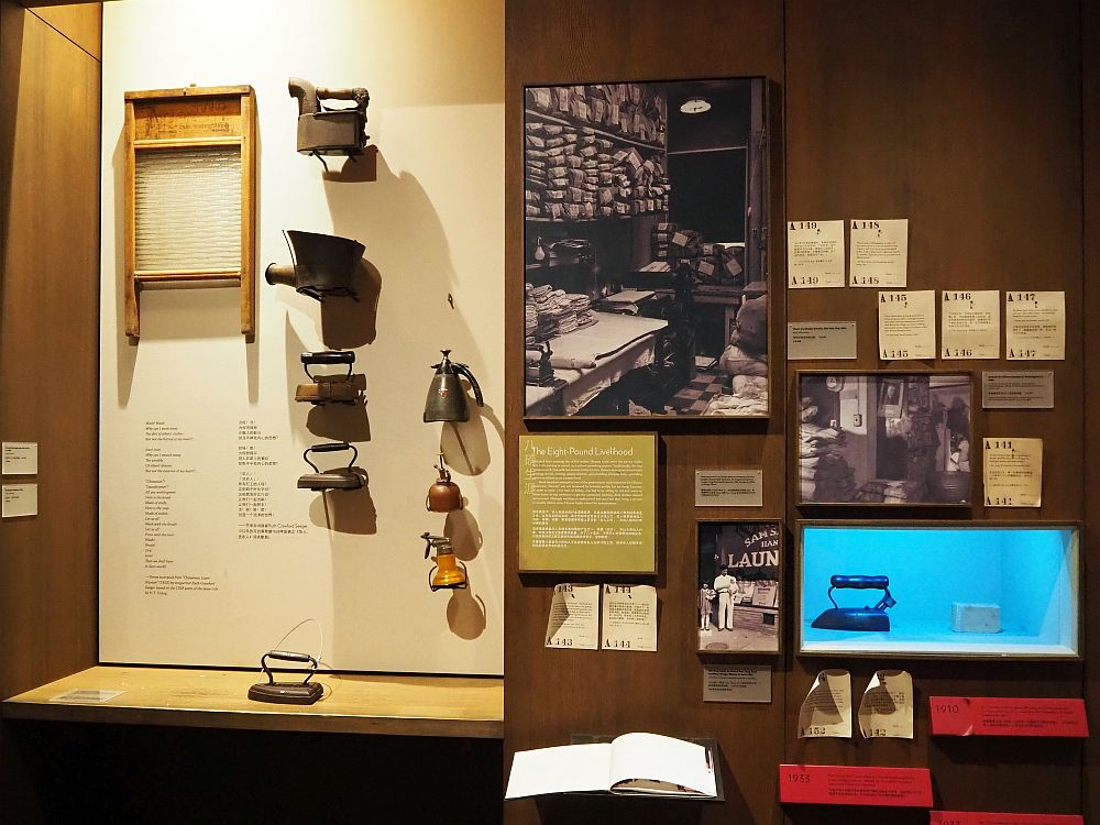 The display contains a number of items. On the left is a washboard and a number of irons and spray cans, along with one iron sitting on a shelf below them. On the right are some historicl photographs of Chinese laundries and various other documents from the period. A sign explains the Chinese laundry phenomenon.