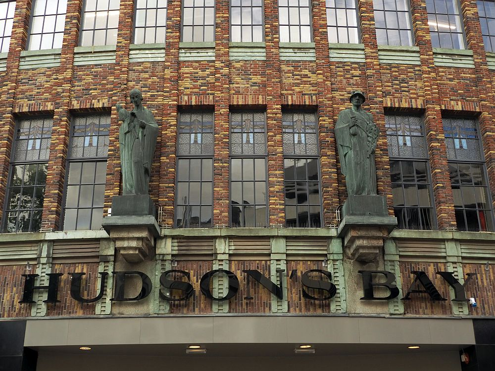 Along the bottom of the picture is the name of the store: Hudson's Bay. Above the lettering are two robed human figures (saints?). Three vertical windows between them and two on each side each have stained glass in their upper panes.