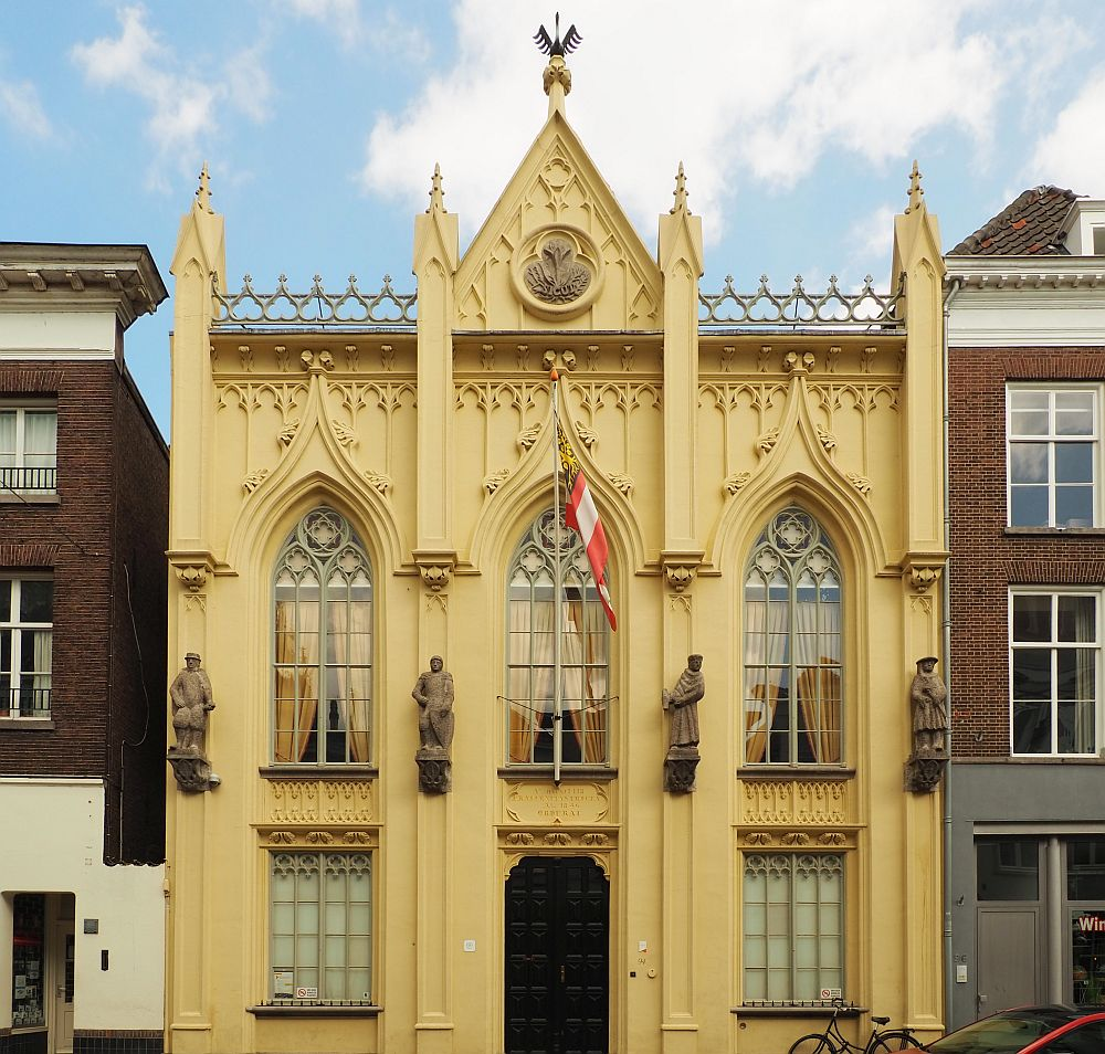 The building has a yellowish plaster with lots of decorative detail. It is two stories tall, with a door in the middle on the ground floor, flanked by one window on either side. On the upper story are three windows in gothic arch shape. The plaster work continues the gothic arch patterning above the windows. Four human figures (saints, maybe?) flank the three windows on the upper story. The roof has a small triangular point above the center window. A decorative medalion is in the center of the triangle and on its top point is a sculpture of a swan.