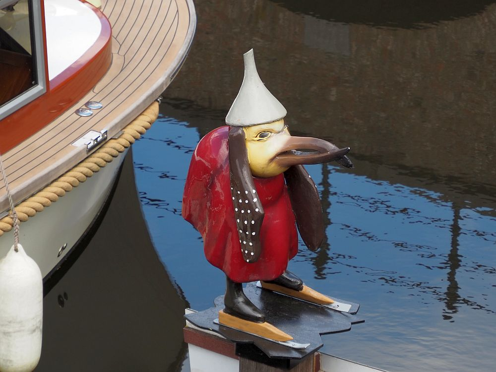 Another strange figure on a pedestal. This one is a bird, with a long beak. IT wears an inverted white funnel on its head and a red robe. It has ears or hair - brown with white polka dots - hanging down on both sides of its head. It stands on ice skates.