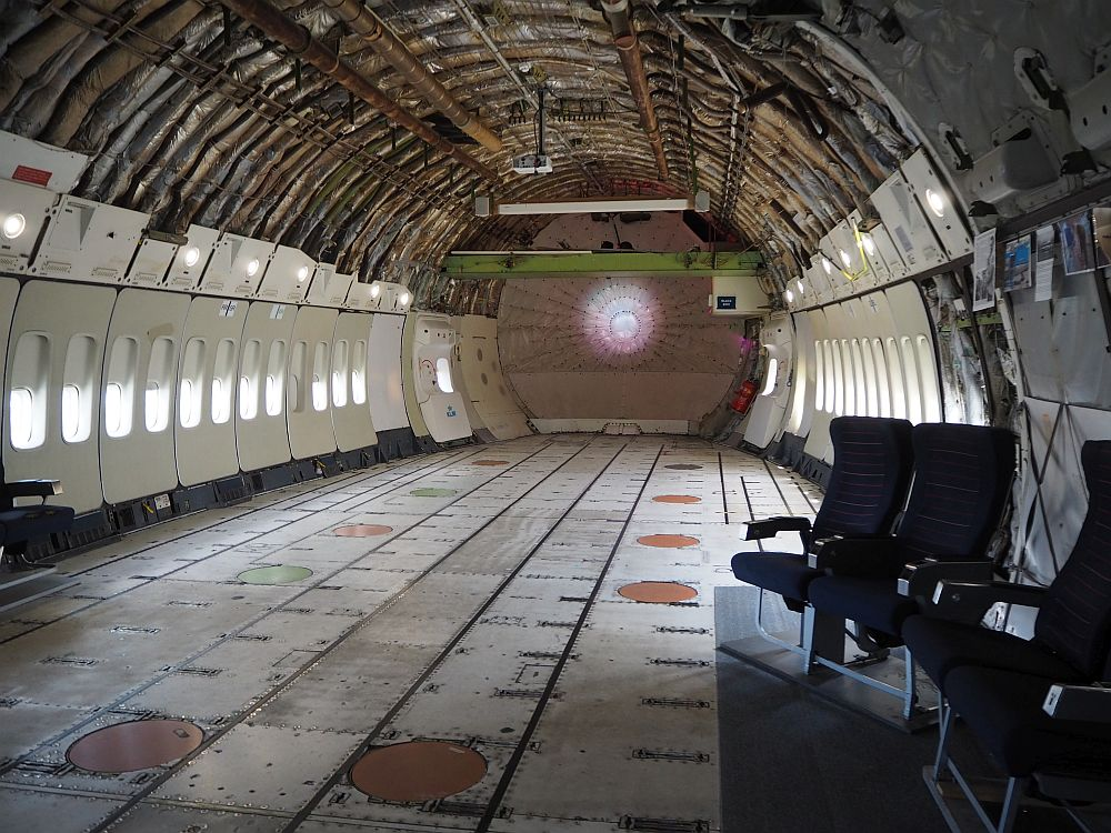 The inside is stripped down to the insulation, which is visible between the struts of the rounded ceiling. The windows still have their plastic panels that we are familiar with from fying, but the panels end at about two meters above the floor. A few airplane chairs have been placed near one wall. The floor is flat but unfinished.
