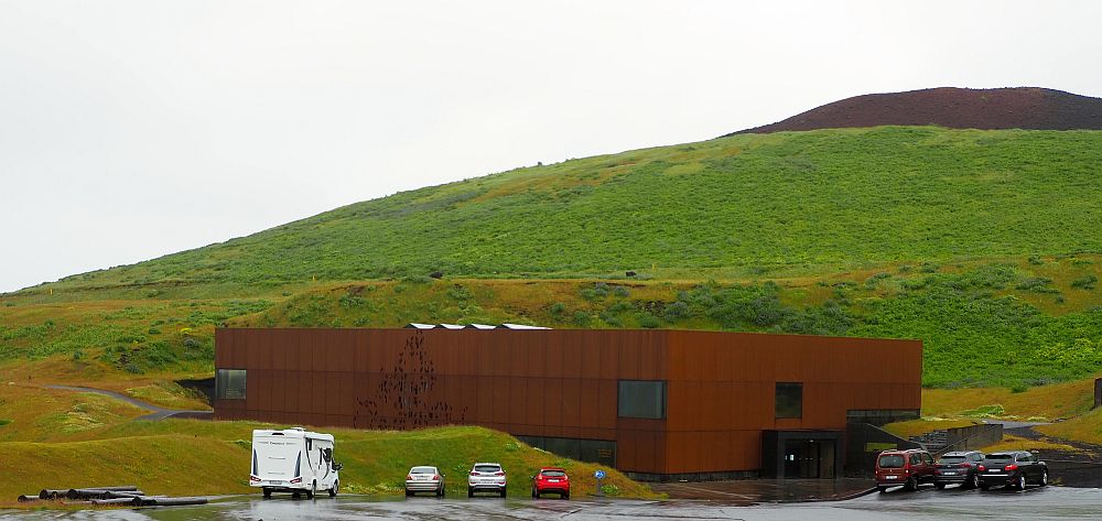The building is a simple, rust-colored block, partly built into the side of the hill/volcano that rises behind it. A few cars are parked in front of the building. The hill behind is covered in grass, except for a very dark brown top.