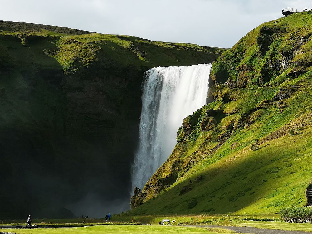 Skogafoss falls off a horizontal shelf in one straight waterfall. On either side of that shelf: green steep hills. A  person at the bottom left gives a sense of the size of this waterfall.