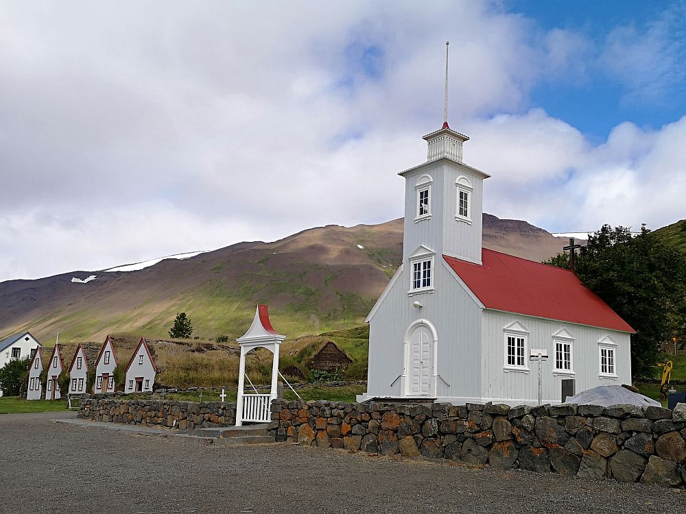 In the forground, the church is white and a simple rectangle, with a door in the short end and a window right above the door, a steeple (perhaps one additional storey tall) above that. The long side of the rectangle that is visible has 3 evenly-spaced windows. The roof is reddish. Beyond the church are the 5 gable fronts of Laufas turf house. Behind them is a mountain.