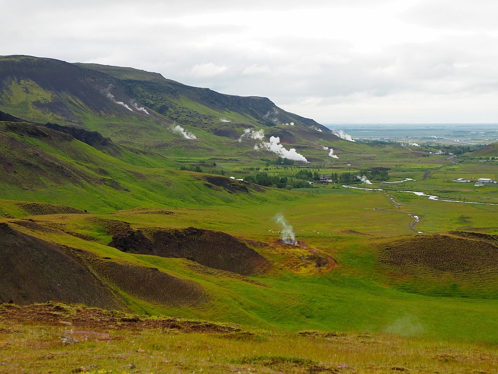 A view down a green valley with a low mountain on the left. Here and there plumes of steam rise from the ground. In the distance, the sea is visible.