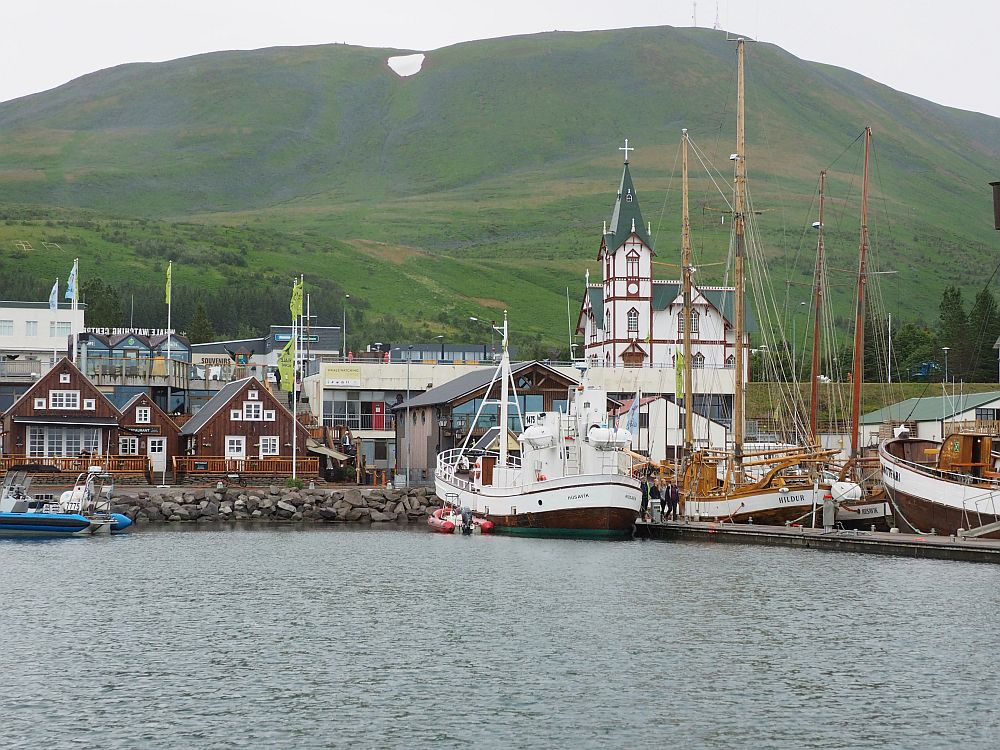 Husavik whale watching leaves from this harbor. Cluster of buildings along the water's edge, closer up than in the image above. Several large oak boats moored along a pier on the right. A white church with a tall tower behind the boats. On the left, a row of 3 red wooden houses with white-framed windows line the waterfront.