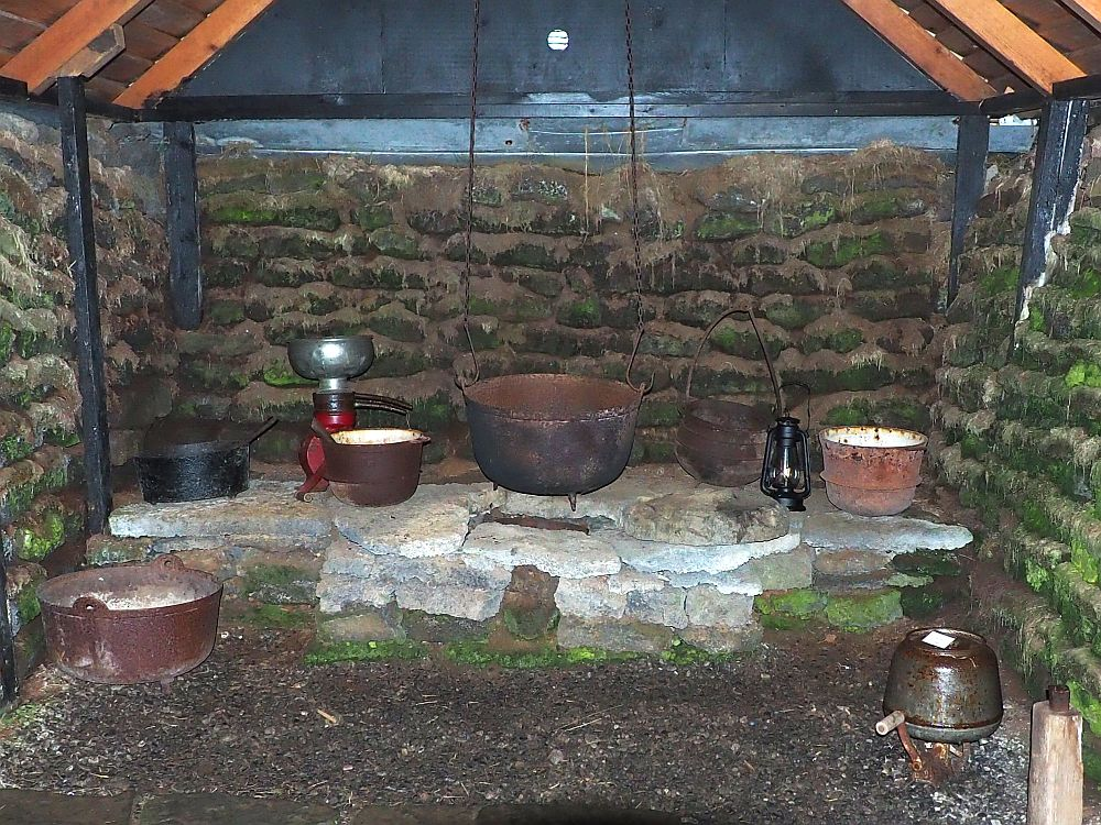 """The """"stove"""" is a pile of flat stones built into the end of the room. On top are several iron pots, and one large pot hangs on chains from the ceiling. The walls behind the stove and on either side are turf, with green moss growing on it in some places. Beams of wood stand vertically against the walls and hold up the beams that support the ceiling."""