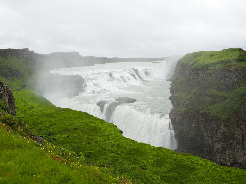 Looking off a cliff to the waterfall in the distance on the opposite side of a canyon. From a distance, the top part of the waterfall looks flat and the water looks all white. It flows toward the camera, then falls off the opposite side of the canyon in a thick white sheet of water.