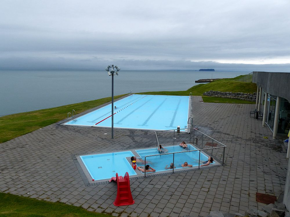 Seen from slightly above, three pools with blue water. Nearest by are two small pools right up against each other: one is a child's wading pool and has a red plastic slide leading into it. The other is a soaking pool and has a number of people sitting on seats along the sides of the pool, soaking. The further pool is more of a normal size, with lanes painted on the bottom and one floating lane divider. Beyond is the sea under a gray sky.