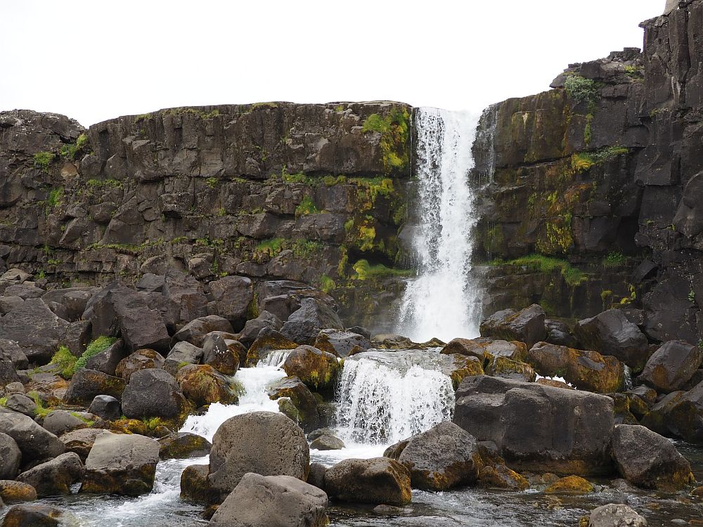 A vertical black cliff with lots of rocks at its bottom. The waterfall is fairly narrow, plunging off the edge of the cliff onto the rocks below.