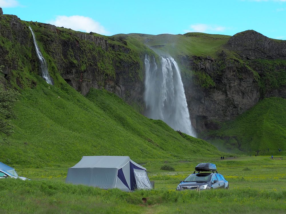 The water falls over a cliff in a veil shape at the back of this picture. In front, at the base of the cliff, is a tent with a car parked next to it. A smaller, narrow waterfall is visible behind the tent to the left.