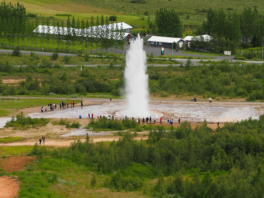 A large flat space as seen from a hill above it. People are visible very small around the edge of the flat area. A huge fountain of white water spouts up in the center of the flat space. Beyond the geyser some low buildings stand across a small street.