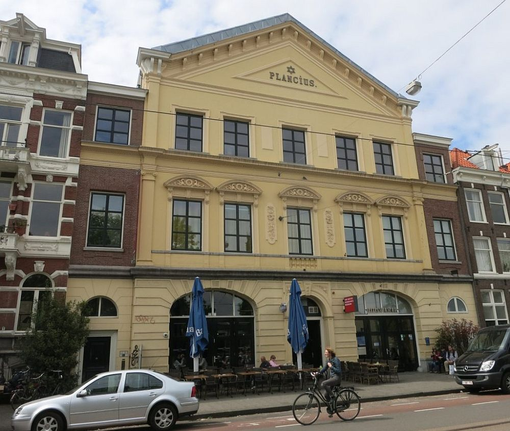"""The building is quite grand: three stories, with the ground floor having arched doorways. The top is a triangle with the word """"Plancius"""" and a small star of David."""