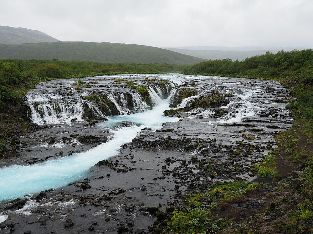 The water flows over flat rocks, then plunges from both sides into a shallow canyon, then down a river to the left in this photo. the water is very blue rather than white, even with a very gray sky.
