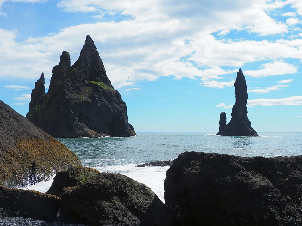 Two rock formations not far off the shore: The left-hand one is bigger and has three points; the right hand one is narrower and has one big point and one smaller one at the side.