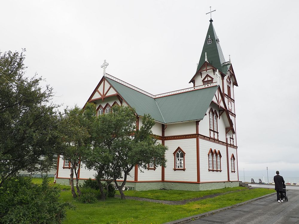 More ornate and bigger than most churches in Iceland, the building is cross-shaped and two storeys tall. The steeple is three stories tall and only narrows at the roof level. The walls are white but the window frames and other edge details are in a brownish-red.