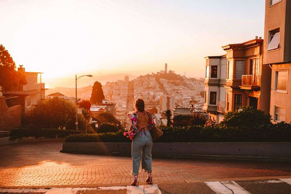 A sunset shot looking at the top curve of Lombard street, with a woman facing down the hill, her back to the camera. A few of the buildings on Lombard street are visible on either side, and in the center distance is a hill with Coit tower showing in sillhouette from the top against an orangy-yellow sky.