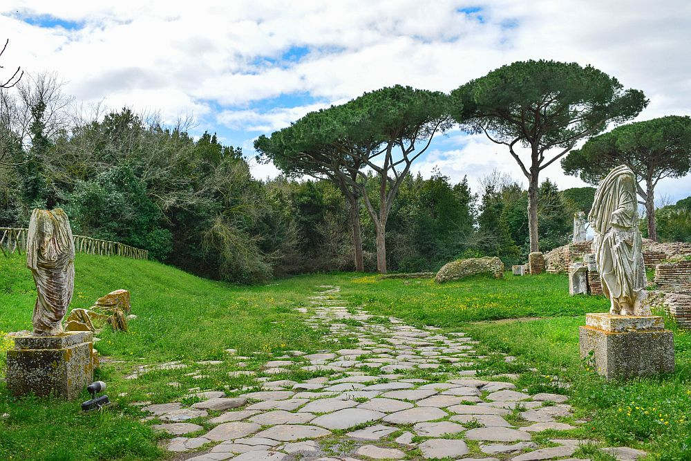 A path is paved in flat stones of various shapes and extends straight ahead into a grassy space. Beyond that it disappears into trees. On the left and the right are two human statues on pedestals. Both are dressed in robes but their heads are missing.