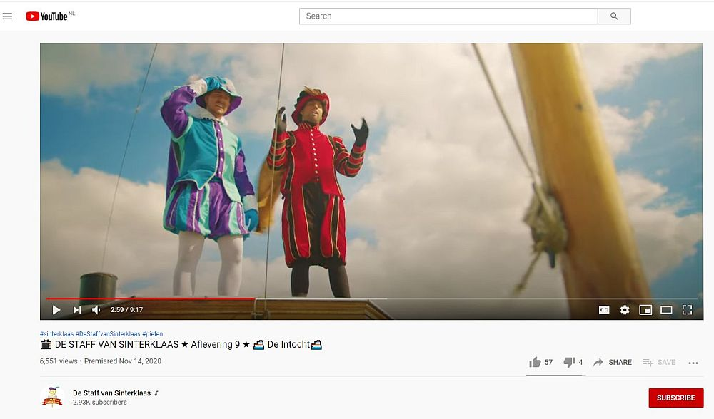 Two Petes stand on a boat (Sinterklaas's steamboat, I think) looking into the distance. They both wear bright outfits: on the left it's turquoise and purple, on the right it's red and brown. Both have snug jackets with puffy sleeves and puffy shorts to above the knee. Both wear tights under that. Neither has a sooty face; they're both white-skinned.