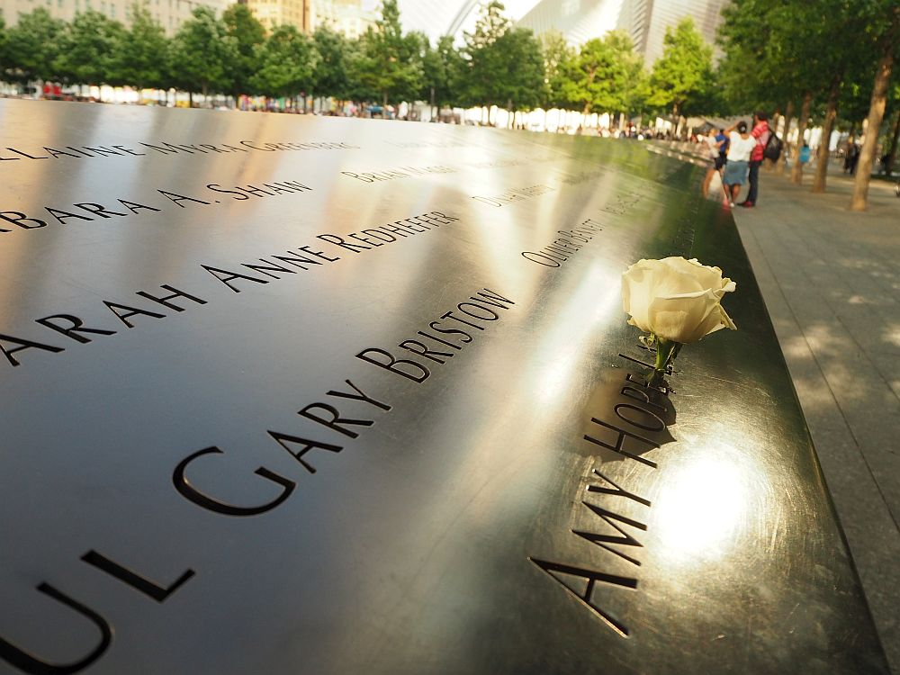 Looking along the bronze parapets of the 9/11 memorial site fountain. It has a flat surface that is tilted. A few names are partly visible: Sarah Anne Redheffer, Gary Bristow, Amy Hope ... her last name is obscured by a white rose that has been inserted into the first letter, L.