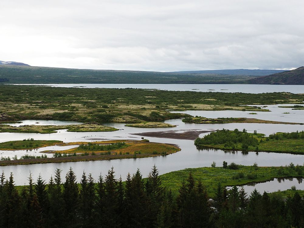Big view over the valley, this time with water in the foreground: a wide river, with several low islands, and a bigger lake in the background. Beyond the lake: low hills. Gray sky above.