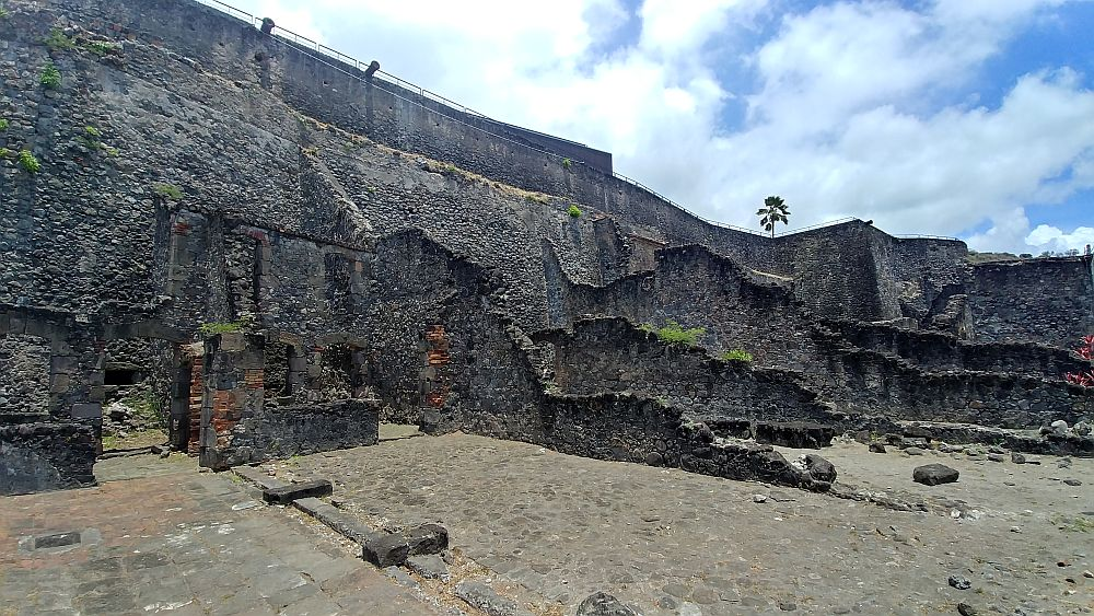 A high wall with crumbling walls sticking out at right angles to it, showing where the rooms of this building used to be. All seem to be made of stone.